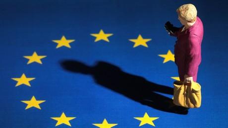 Symbolbild: Miniaturfigur der Bundeskanzlerin steht allein auf einer EU Flagge und wirft einen langen Schatten auf die EU.