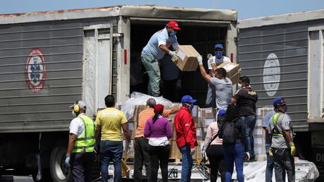 Während der nationalen Quarantäne aufgrund der Ausbreitung des Coronavirus in Venezuela entladen Arbeiter am 28. März am Simón Bolívar International Airport in Caracas Hilfslieferungen aus China.