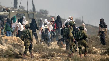 Im Schutz von bewaffneten israelischen Soldaten werfen extremistische Siedler Steine auf Palästinenser, die gegen den Bau einer illegalen Siedlung bei Turmus Ayya protestieren (Bild vom 17.10.19).