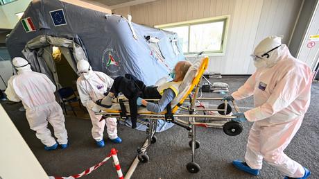 Mediziner in Schutzanzügen bringen am 7.04.2020 einen Patienten  in das Erste-Hilfe-Zelt des Krankenhauses Policlinico di Tor Vergata in Rom. Hier weden Menschen mit COVID-19-Symptomen zur Behandlung eingeliefert.