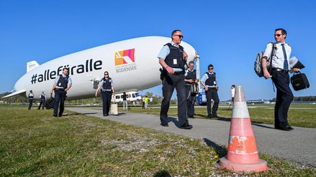Sechs Beamte kontrollieren von Bord eines Zeppelins aus, ob sich die Menschen an die Regeln zur Eindämmung des Coronavirus halten