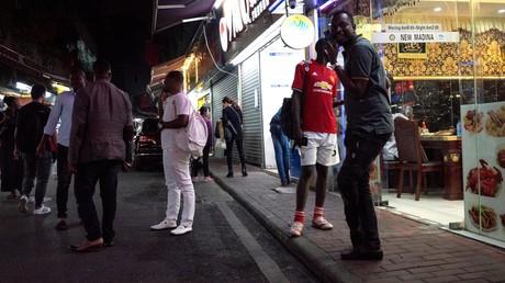Menschen versammeln sich auf einer Straße im Bezirk
