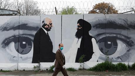 Ein Afghane mit Gesichtsmaske geht in Kabul an einer Wand vorbei, die mit einem Graffiti von Zalmay Khalilzad, dem US-Beauftragten für den Frieden in Afghanistan, und Mullah Abdul Ghani Baradar, dem Leiter der Taliban-Delegation, bemalt ist.