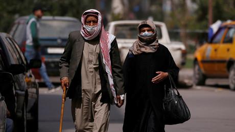 Ein Mann und eine Frau gehen mit Gesichtsmasken durch die Straßen von Damaskus. Zur Eindämmung der Corona-Pandemie wurden auch in Syriens Hauptstadt Ausgehsperren verhängt. (24. März 2020)