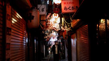Ein Mann mit einer Gesichtsmaske geht durch eine Straße mit geschlossenen Restaurants und Bars in Tokio, nachdem die Regierung aufgrund der COVID-19-Krise den Ausnahmezustand verhängte.