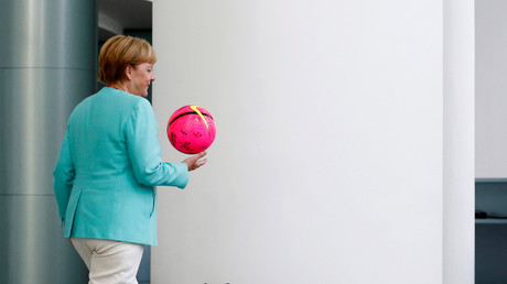 Bundeskanzlerin Angela Merkel mit dem Ball, den sie von internationalen Fußballerinnen des Projekts