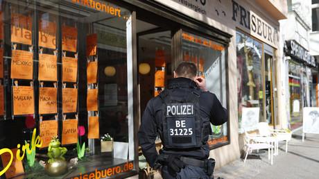 (Symbolfoto) Ein Polizist steht vor einem Reisebüro im Berliner Stadtteil Steglitz