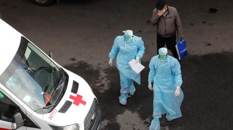 Symbolbild: Ärzte und ein Mann mit Schutzmaske in der Nähe eines Krankenhauses in Sankt Petersburg