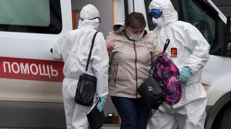 Eine COVID-19-Patientin steigt aus dem Rettungswagen in Moskau aus.