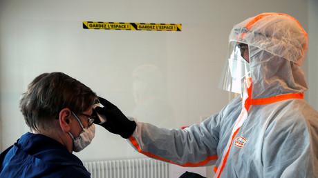 Ein französischer Arzt kontrolliert die Körpertemperatur einer Frau in einem Testgebiet für Coronavirus-Erkrankung in Gouzeaucourt.