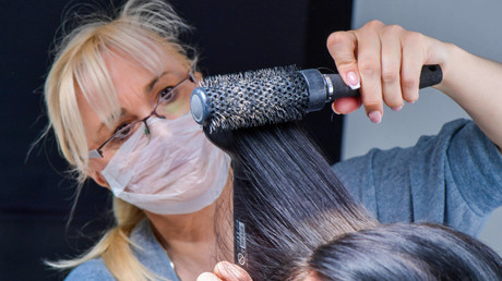(Symbolbild) Eine Friseurin mit Mundschutz föhnt einer Kundin die Haare. Ab 4. Mai haben die Friseursalons bundesweit wieder auf. Es gelten jedoch besondere Hygienevorschriften.
