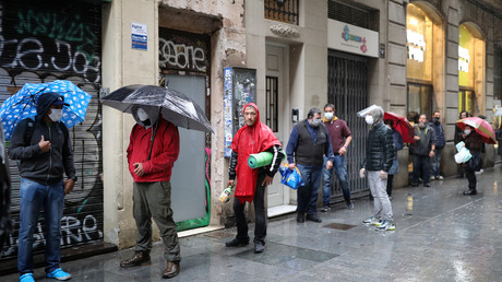 Menschen in Barcelona warten vor der Pfarrkirche Santa Anna in Barcelona auf kostenlose Essenspakete,
