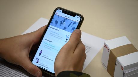 Ein Schweizer Soldat hält sein Smartphone in der Hand, auf dem eine von der Eidgenössischen Technischen Hochschule Lausanne (EPFL) entwickelte App zu sehen ist. Sie soll ermöglichen, diejenigen zu finden, die in engem Kontakt mit jemandem standen, der positiv auf das Coronavirus getestet wurde.