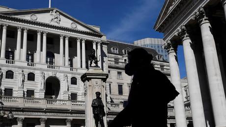 Eine Person mit einer Maske geht in London an der Bank of England vorbei