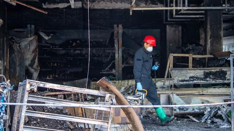 Ein Ermittler untersucht am 30. April ein ausgebranntes türkisches Geschäft im bayerischen Waldkraiburg. Drei Tage zuvor war der Laden eines türkischen Gemüsehändlers in Flammen aufgegangen.