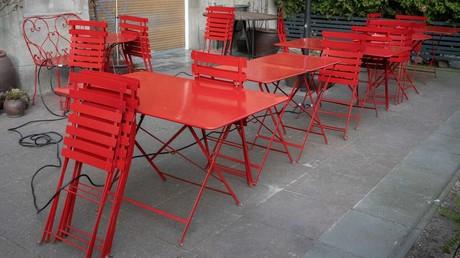 Zusammengeklappte Stühle und leere Tische auf der Terrasse eines Restaurants im Berliner Bezirk Kreuzberg. Wegen der Corona-Pandemie durften die Gaststätten keine Gäste bewirten. Ab 15. Mai sollen nun in Berlin die Lokale wieder öffnen.