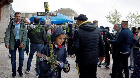 Ein Mädchen trägt am 12. Mai 2020 ein mit Blumen geschmücktes Kreuz während einer Pilgerfahrt zum mittelalterlichen Ostrog-Kloster in der Nähe der Stadt Nikšić. Später wurden mehrere Geistliche unter dem Vorwurf, sie hätten die massenhafte Versammlung organisiert, verhaftet.