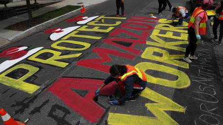 Aktivisten malen gegenüber dem Wohnsitz von Amazon-Chef Jeff Bezos eine Losung auf die Straße, Washington, USA, 29. April 2020.