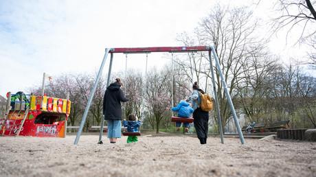 Zwei Mütter schaukeln ihre Kinder auf einem Spielplatz. Wegen des Coronavirus bieten die Kindertagesstätten seit Wochen nur noch Notbetreuung an. Das stellt Millionen von Eltern vor große Herausforderungen.