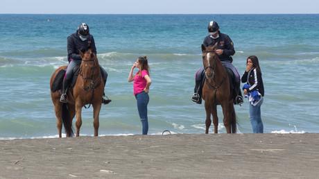 Symbolbild: Polizisten überprüfen die Dokumente zwei junger Frauen, die am Strand von Ostia bei Rom ein Sonnenbad nehmen wollten.