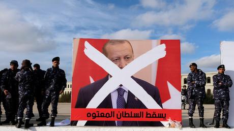 Sicherheitskräfte stehen bei einer Demonstration in Bengasi gegen die türkische Einmischung in Libyen neben einem Plakat des türkischen Präsidenten Recep Tayyip Erdoğan.