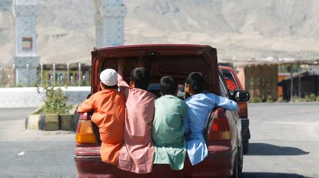 Afghanische Jungen fahren im Kofferraum eines Autos während des Eid al-Fitr, dem muslimischen Fest zum Ende des heiligen Fastenmonats Ramadan in der Provinz Laghman in Afghanistan, 24. Mai 2020.