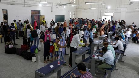 Wanderarbeiter und ihre Familien stehen Schlange, um sich für Zugfahrten in ihre Heimat registrieren zu lassen