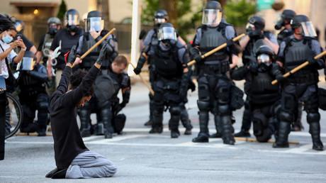 Ein Demonstrant kniet vor einer Gruppe Polizisten (Atlanta, Georgia, 1. Juni 2020)