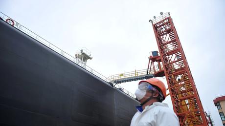 Ein Hafenarbeiter in der Nähe eines Öltankers im Hafen von Qingdao, China