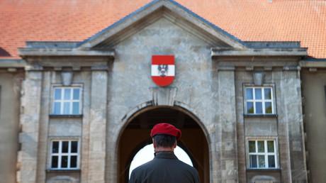Symbolbild: Ein Soldat des Österreichischen Bundesheer mir roter Kappe vor dem Staatswappen in der Maria-Theresien-Kaserne  in Wien
