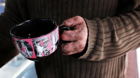 Nach dem Lockdown brechen Wirtschaft und Gesundheitswesen des Westens zusammen – mit Millionen Toten (Symbolbild: Obdachloser hält Tasse für Spenden hin . New York, 07.04.2015)