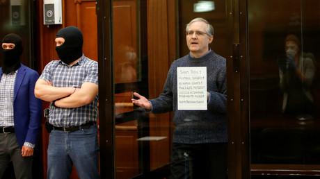Paul Whelan hält während der Urteilsverkündung ein Plakat in der Hand, um gegen den Prozess zu protestieren.