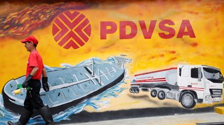 Das staatliche venezolanische Ölunternehmen PDVSA ist gezwungen, die Produktion weiter zu drosseln. (Symbolbild: Arbeiter vor einem Wandbild mit dem PDVSA-Logo an einer Tankstelle in Caracas, 29. August 2014)