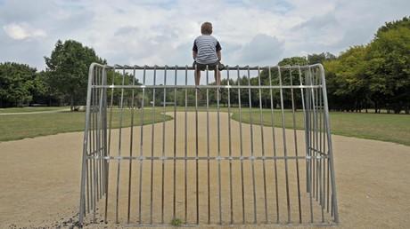 (Symbolfoto) Ein neunjähriger Junge sitzt einsam auf einem Metalltor auf einem Mini-Fußballfeld. Kinder werden eher Opfer von sexuellem Missbrauch als Opfer eines Verkehrsunfalls, meinen Experten.