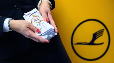 Symbolbild vom 17. Juni 2020: Eine Lufthansa-Flugbegleiterin am Frankfurter Flughafen verteilt Hygiene-Tücher