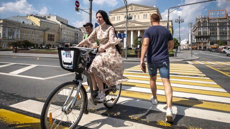 Fußgänger und Radfahrer vor dem Bolschoi-Theater in Moskau