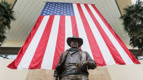(Symbolbild). Eine Statue von John Wayne unter einer US-Flagge auf dem John Wayne Airport in Orange County am 28. Juni 2020 in Santa Ana, Kalifornien.