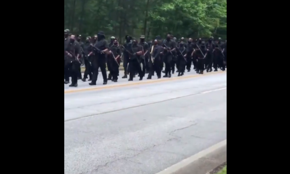 Hunderte von schwer bewaffneten afroamerikanischen Demonstranten marschieren durch Georgia