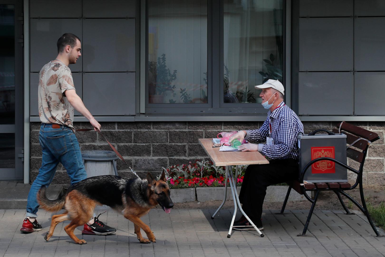 Ein Mitarbeiter eines Freiluftwahllokals in Sankt Petersburg spricht mit einem Mann, der mit seinem Hund Gassi geht, 25. Juni 2020.