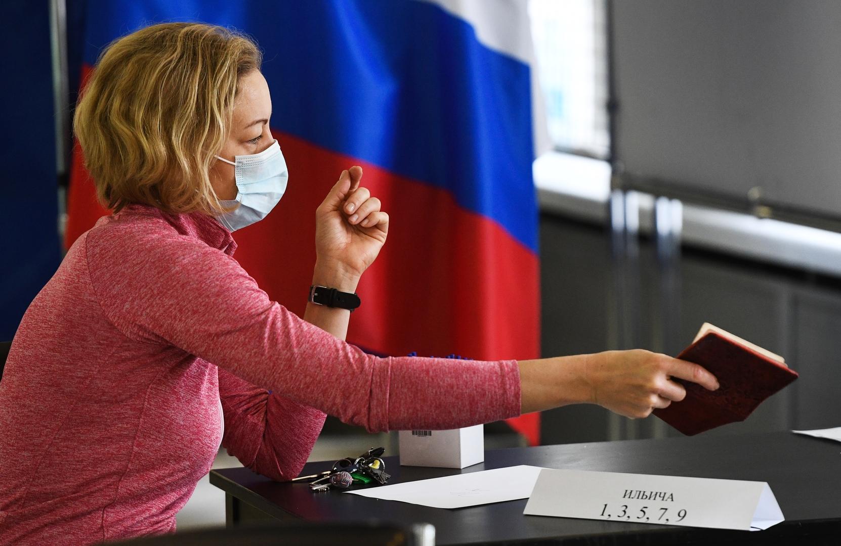Eine Frau zeigt ihren Pass in einem Wahllokal in Nowosibirsk, um den Stimmzettel zu bekommen, 1. Juli 2020.