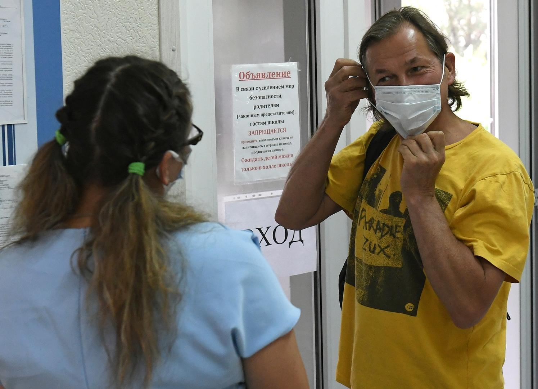 Ein Mann zieht sich eine Schutzmaske an, bevor er ein Wahllokal in Sajanogorsk betritt, 1. Juli 2020.