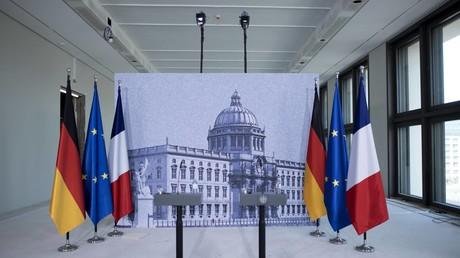 Symbolbild: Die Fahnen Deutschlands, Frankreichs und der EU stehen neben zwei Pulten, an denen Macron und Merkel sprechen werden (Berlin, 19. April 2018)
