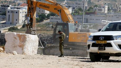 Ein Bagger entfernt unter Aufsicht eines israelischen Soldaten Steinblöcke, die von Palästinensern in Hebron im israelisch besetzten Westjordanland aufgestellt wurden. 2. Juli 2020.
