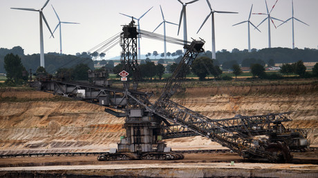 Hinter einem Schaufelradbagger im Braunkohletagebau Garzweiler in Nordrhein-Westfalen drehen sich Windräder zur Stromerzeugung. Der Bundestag hat am Freitag den schrittweisen Kohleausstieg in Deutschland bis spätestens 2038 beschlossen.