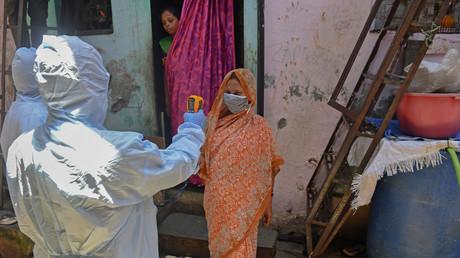 Archivbild vom 24. Juni: Ärzte führen in den Slums von Dharavi in der indischen Metropole Mumbai ein medizinisches Screening durch, indem sie bei der Bevölkerung Fieber messen