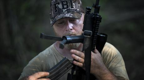 Milizkommandeur sagt Bürgerkrieg 2021 und Niedergang der USA voraus – weist Rassismusvorwürfe zurück (Chris Hill, Gründer des Zweigs der bewaffneten Miliz Security Force III% im US-Bundesstaat Georgia, lädt ein Gewehr bei einer Feldübung. Jackson, Georgia, USA. 29. Juli 2017)