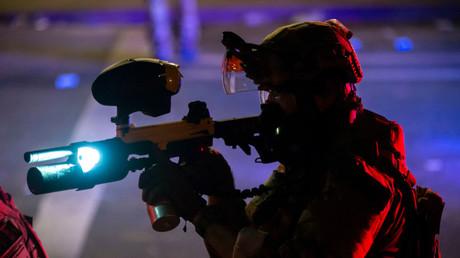 Ein US-amerikanischer Bundespolizist zielt mit einer sogenannten Pepperball-Waffe auf Demonstranten, 22. Juli 2020 in Portland, Oregon, USA.
