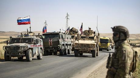 US-Soldaten stehen in der Nähe eines russischen Militärfahrzeugs in der nordost-syrischen Stadt al-Malikiya (Dêrik) an der Grenze zur Türkei. (3. Juni 2020)