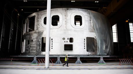 Ein Techniker beim Beginn der Montagephase der Kernfusionsanlage ITER nach dem Tokamak-Prinzip am unteren Zylinder des Kryostaten, der für das Hochvakuum und die tiefen Temperaturen des Vakuumgefäßes und der supraleitenden Magnete sorgt.
