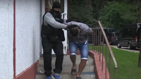 Mitglieder der weißrussischen Sondereinheit führen festgenommene russische Staatsbürger einzeln ab.